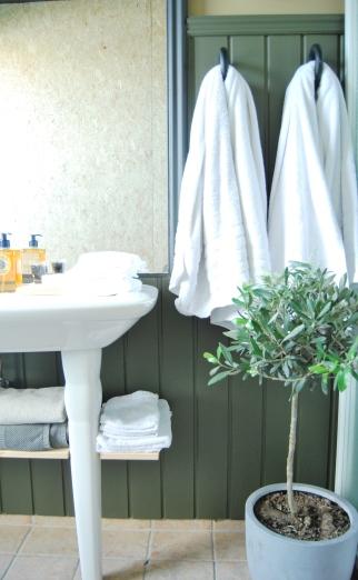 Istedenfor skaper, henger det nå håndklær ved siden av dusjen. Den mørke fargen på veggen demper hele uttrykket